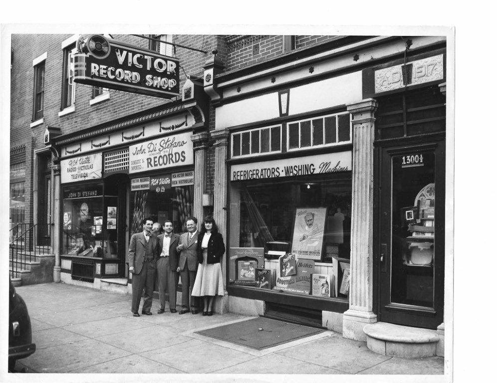 (circa 1924) Shows the café as it's original beginning as a record shop across the street from it's present location. It opened in 1918. The middle 2 men are my father and grandfather (the founder).